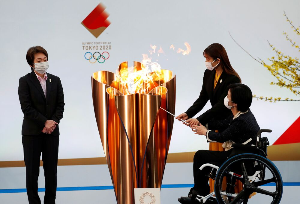 Tokyo 2020 President Seiko Hashimoto looks on as actress Satomi Ishihara and Paralympian Aki Taguchi light the celebration cauldron on the first day of the Tokyo 2020 Olympic torch relay in Naraha, Fukushima prefecture, Japan, 25 March 2021.