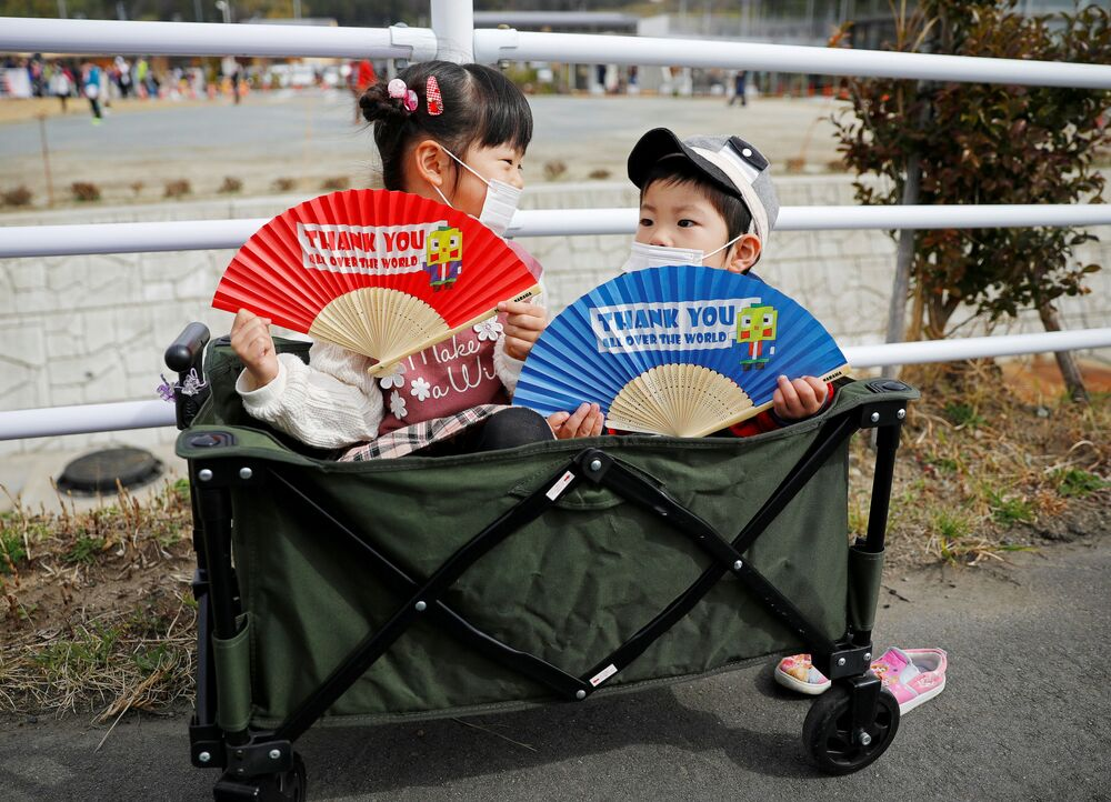 Children wearing face masks hold fans as they wait along the route of the Tokyo 2020 Olympic torch relay, in the midst of the coronavirus disease (COVID-19) pandemic, in Naraha, Fukushima prefecture, Japan, 25 March 2021.