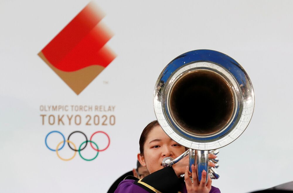 A member of the marching band Seeds+ plays a trumpet during the opening performance on the first day of the Tokyo 2020 Olympic torch relay in Naraha, Fukushima prefecture, Japan, 25 March  2021.