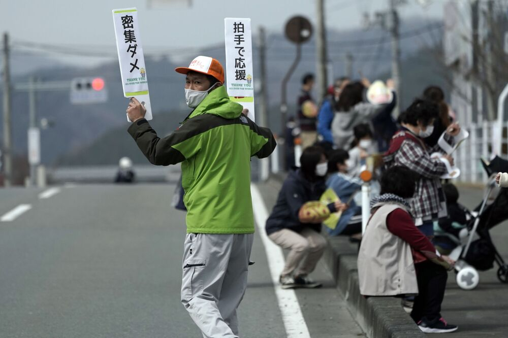 A local sign contains announcements to bystanders - No crowding, left, and hand clapping to cheer - for the benefit of torchbearers at the torch relay route of the first section of the Fukushima Torch Relay in Naraha, Fukushima prefecture, northeastern Japan, Thursday, 25 March 2021. The torch relay for the postponed Tokyo Olympics began its 121-day journey across Japan on Thursday and is headed toward the opening ceremony in Tokyo on 23 July 2021.