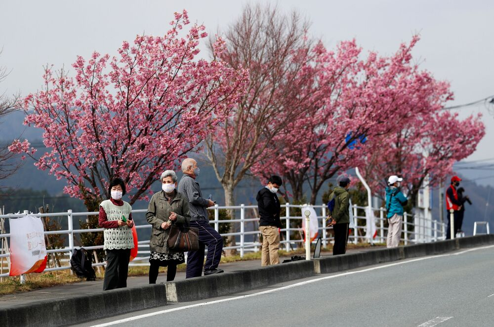 People wearing face masks wait under blooming cherry blossom trees along the route of the Tokyo 2020 Olympic torch relay, in the midst of the coronavirus disease (COVID-19) pandemic, in Naraha, Fukushima prefecture, Japan, 25 March 2021.