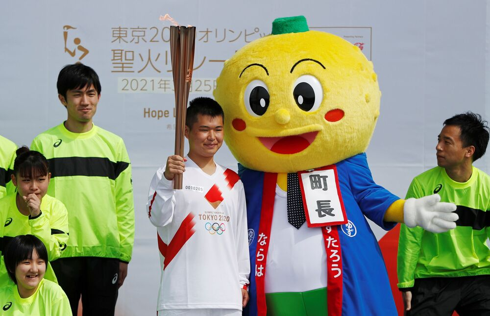 A torchbearer poses with Naraha town mascot Yuzutaro after running his leg of the Tokyo 2020 Olympic torch relay, on the first day of the relay in Naraha, Fukushima prefecture, Japan, 25 March 2021.