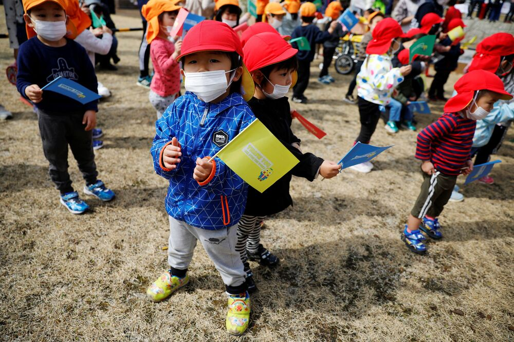 Children wearing face masks wait along the route of the Tokyo 2020 Olympic torch relay on the first day of the relay in Naraha, Fukushima prefecture, Japan, 25 March 2021.