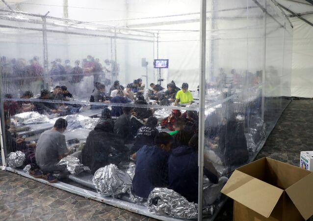 Migrants sit inside a temporary processing facility for migrants, including unaccompanied minors, in Donna, Texas, U.S. March 17, 2021