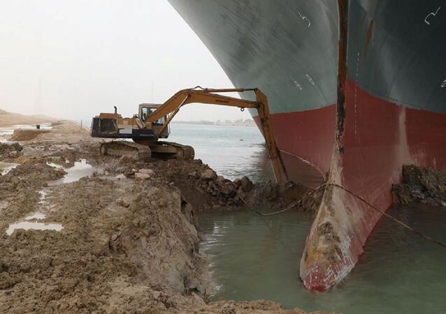 An excavator attempts to free stranded container ship Ever Given, one of the world's largest container ships, after it ran aground, in the Suez Canal, Egypt 25 March 2021.
