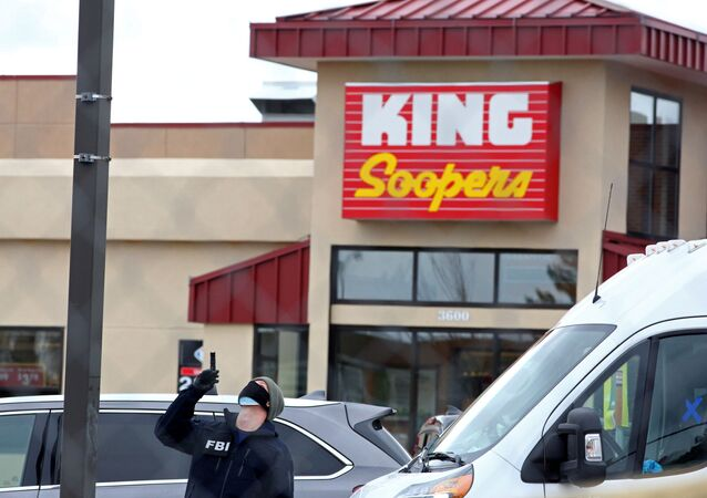 An FBI agent surveys the site of a mass shooting at a King Soopers grocery store in Boulder, Colorado, U.S. March 23, 2021.