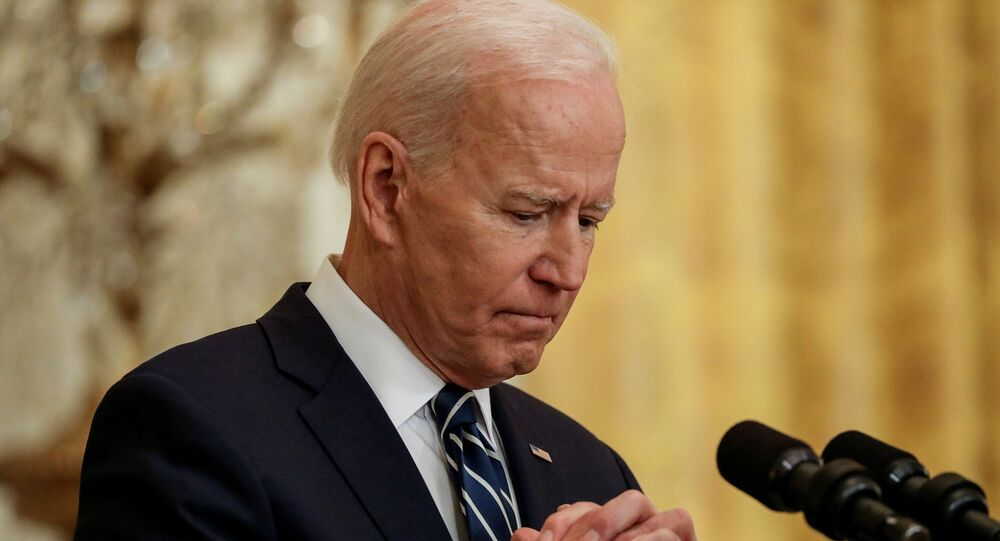 U.S. President Joe Biden clasps his hands as he holds his first formal news conference in the East Room of the White House in Washington, U.S., March 25, 2021