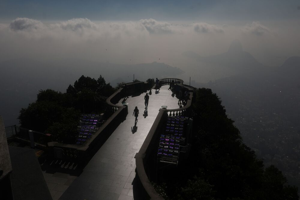 People visit the Christ the Redeemer statue during the statue's restoration, as work is underway ahead of its 90th anniversary, in Rio de Janeiro, Brazil, 24 March 2021.