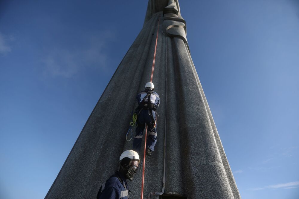 Workers climb the Christ the Redeemer statue for restoration, as work is underway ahead of its 90th anniversary, in Rio de Janeiro, Brazil, 24 March 2021.