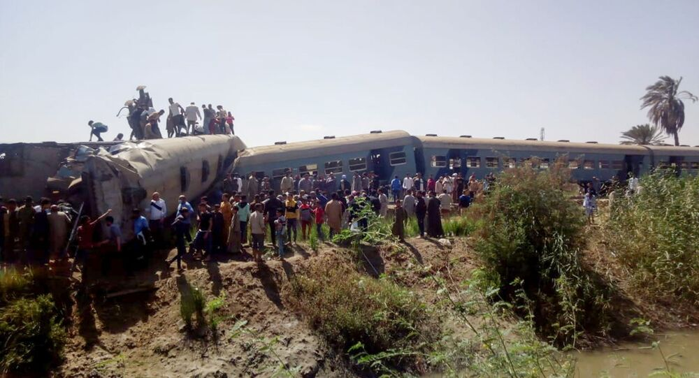 People inspect the damage after two trains have collided near the city of Sohag, Egypt, March 26, 2021