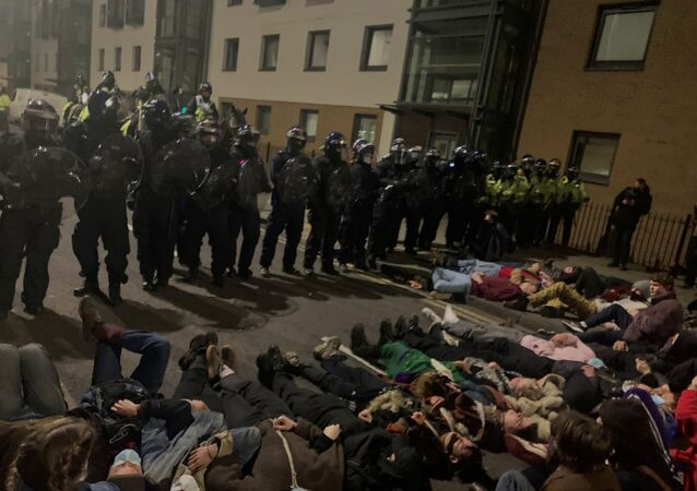 Police officers stand in position as protesters demonstrate against new policing laws in Bristol, Britain, early March 24, 2021, in this picture obtained from social media.