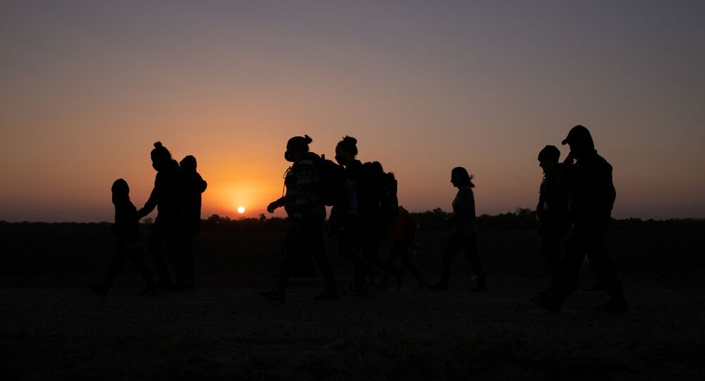 The sun rises as asylum-seeking migrants' families from Honduras and El Salvador walk towards the border wall after crossing the Rio Grande river into the United States from Mexico on a raft, in Penitas, Texas, 26 March 2021