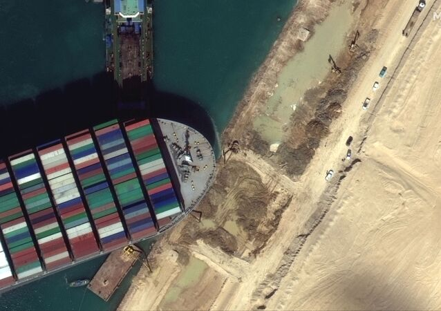 A view of the earth moving equipment excavating sand near the bow of the Ever Given container ship, in Suez Canal in this Maxar Technologies satellite image taken on March 27, 2021