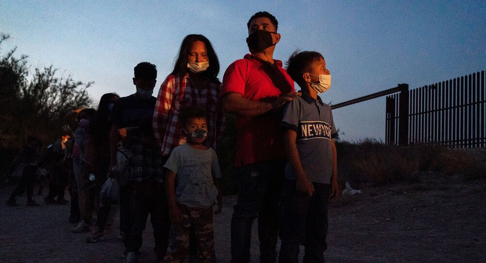 Asylum-seeking migrants' families make a line to board a bus as they wait to be transported by the U.S. Border Patrols after crossing the Rio Grande river into the United States from Mexico in Penitas, Texas, U.S., March 26, 2021.