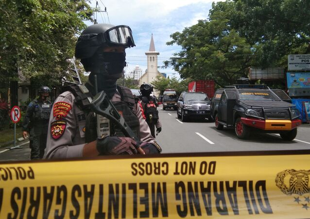 Armed police officers stand guard along a closed road following an explosion outside a Catholic church in Makassar, South Sulawesi province, Indonesia, March 28, 2021 in this photo taken by Antara Foto.  Antara Foto/Arnas Padda/ via REUTERS  ATTENTION EDITORS - THIS IMAGE WAS PROVIDED BY A THIRD PARTY. MANDATORY CREDIT. INDONESIA OUT.