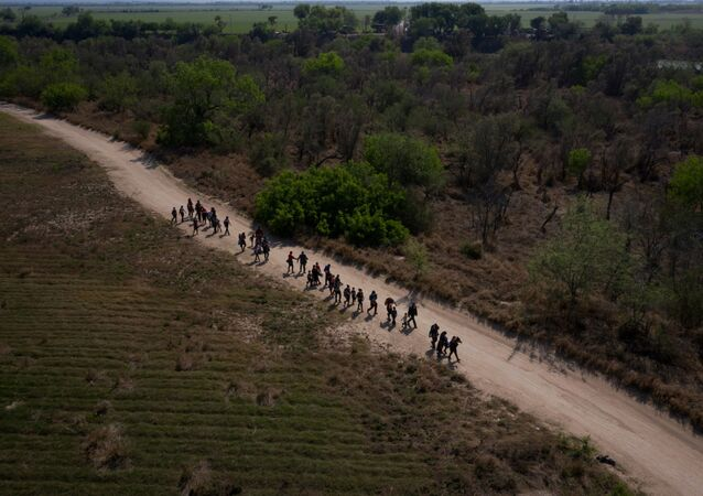 Asylum seeking migrant families from Central America walk towards the border wall after crossing the Rio Grande river into the United States from Mexico on rafts in Penitas, Texas, U.S., March 26, 2021
