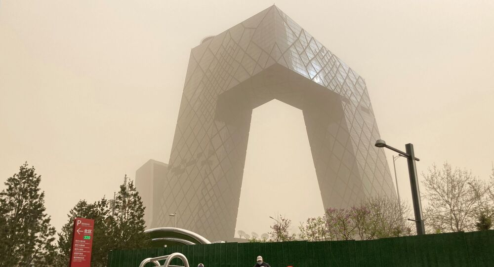 Construction workers are seen in front of the CCTV headquarters shrouded in dust as the city is hit by a sandstorm, in Beijing, China March 28, 2021.