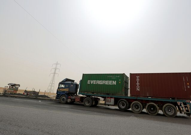 A truck carrying Evergreen and Triton containers waits to pass through the main gate of the El Ain El Sokhna port to the Suez Canal in dusty weather, 24 March 2021