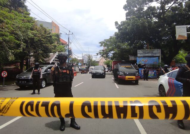 Armed police officers stand guard along a closed road following an explosion outside a Catholic church in Makassar, South Sulawesi province, Indonesia, March 28, 2021.