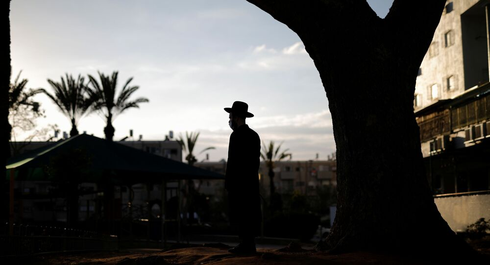 An ultra-Orthodox Jewish man looks on as others dip cooking utensils in boiling water to remove remains of leaven in preparation for the upcoming Jewish holiday of Passover as the country begins to emerge from coronavirus disease (COVID-19) pandemic closures due to it's rapid vaccine roll-out, in Ashdod, Israel March 25, 2021.