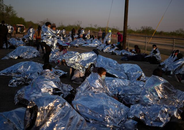 Linda, an asylum-seeking migrant from Honduras, awakes at sunrise next to others who took refuge near a baseball field after crossing the Rio Grande river into the United States from Mexico on rafts, in La Joya, Texas, U.S., March 19, 2021.