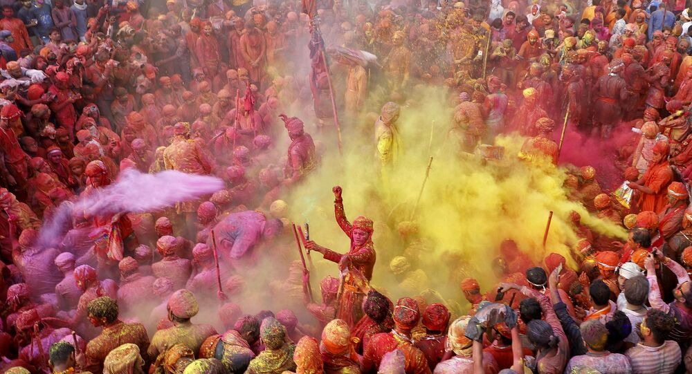 Men daubed in colours throw coloured powder at each other during Lathmar Holi celebrations, amidst the spread of the coronavirus disease (COVID-19), in the town of Nandgaon, in the northern state of Uttar Pradesh, India, March 24, 2021.