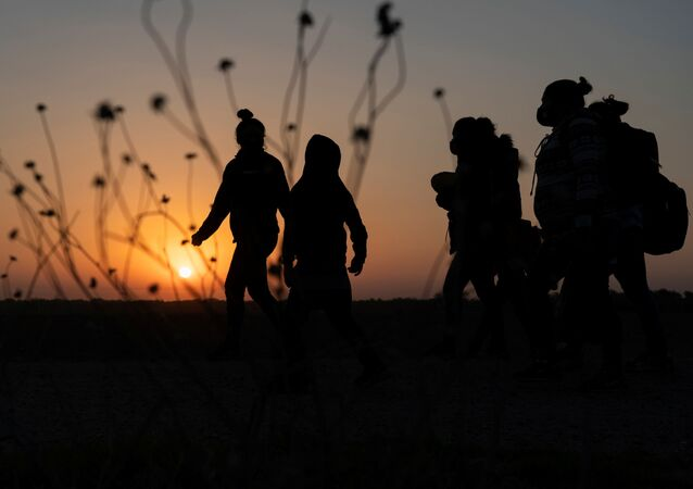 Asylum-seeking migrants' families walk towards the border wall after crossing the Rio Grande river into the United States from Mexico, in Penitas, Texas, U.S., March 26, 2021.