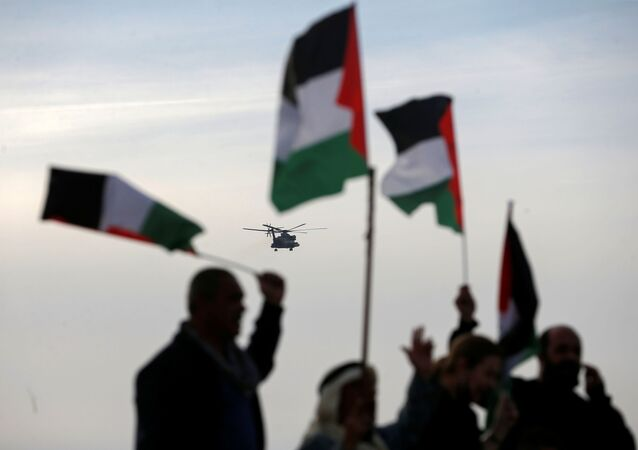Demonstrators hold Palestinian flags as an aircraft carrying Israeli Prime Minister Benjamin approaches to land near the heritage site of ancient Susya, during a protest against Netanyahu's visit to the site, in Susya village in the Israeli-occupied West Bank March 14, 2021.