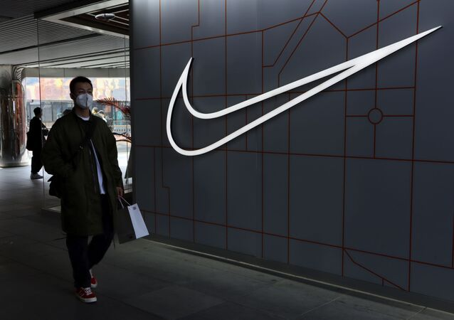 A man walks past a store of the sporting goods retailer Nike Inc at a shopping complex in Beijing, China March 25, 2021