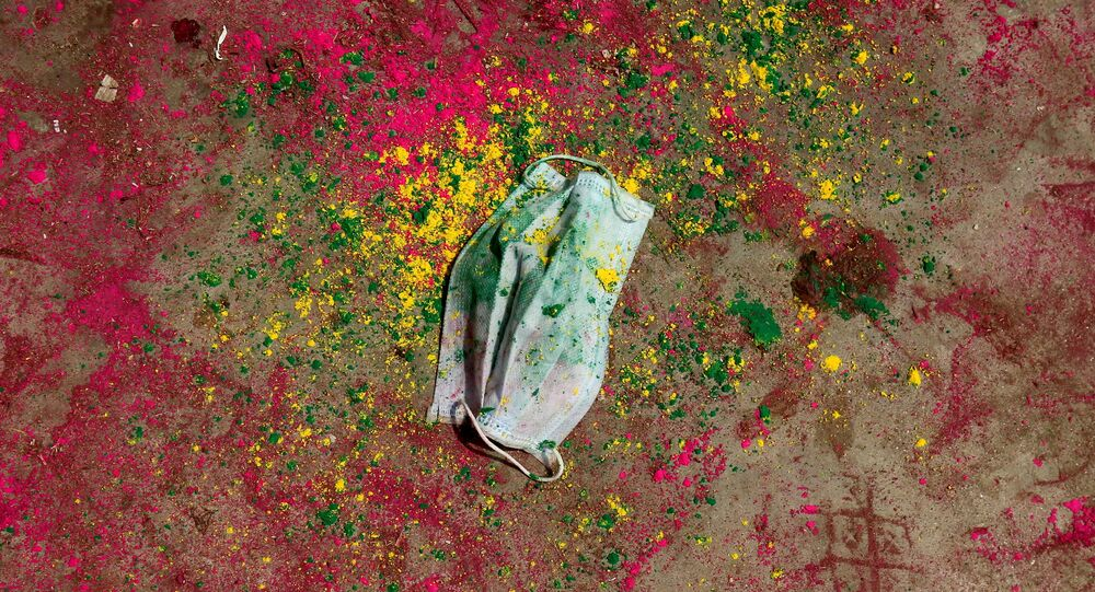 A face mask lies on a road covered with colour powder during Holi celebrations, amidst the spread of the coronavirus disease (COVID-19), in Chennai, India, March 29, 2021.