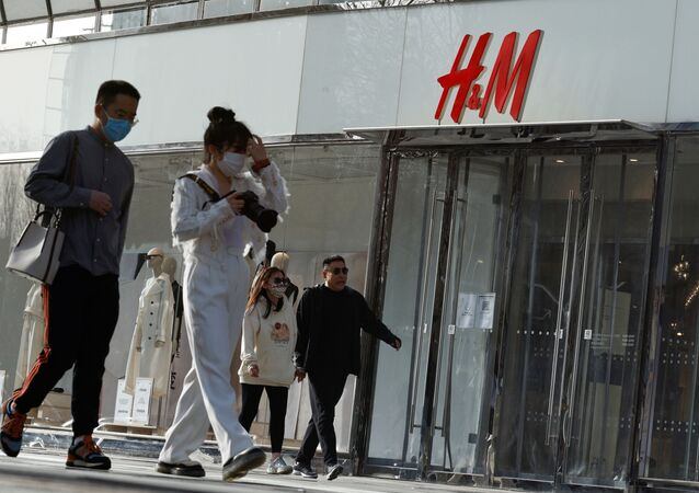 People walk past an H&M store in a shopping area in Beijing, China, 28 March 2021
