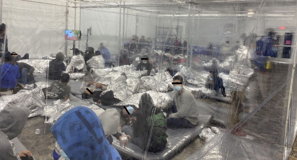 Migrants crowd a room with walls of plastic sheeting at the U.S. Customs and Border Protection temporary processing center in Donna, Texas, U.S. in a recent photograph released March 22, 2021