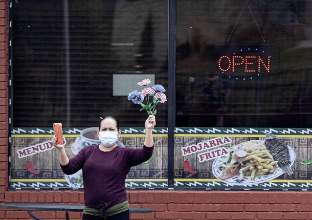 A woman holds plastic flowers as the motorcade of U.S. President Joe Biden drives past following a visits to the Centers for Disease Control and Prevention (CDC) in Atlanta, Georgia, U.S., March 19, 2021.