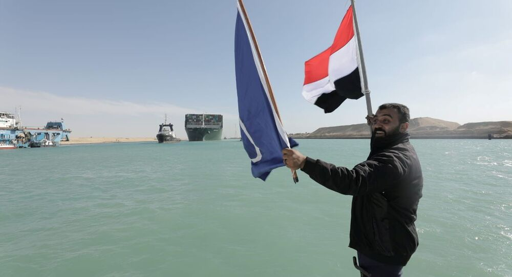 A man waves an Egyptian flag as ship Ever Given, one of the world's largest container ships, is seen after it was fully floated in Suez Canal, Egypt March 29, 2021.