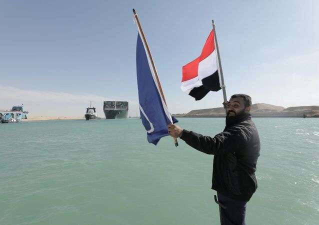 A man waves an Egyptian flag as the Ever Given, one of the world's largest container ships, is seen after it was fully floated in the Suez Canal, Egypt 29 March 2021.
