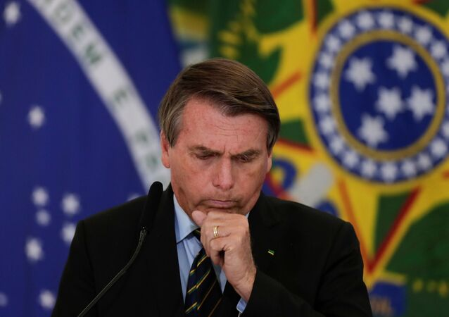Brazil's President Jair Bolsonaro coughs during a ceremony to announce measures by Caixa Economica bank in support of philanthropic hospitals, in Brasilia, Brazil March 25, 2021.