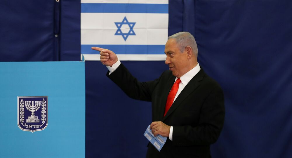 FILE PHOTO: Israeli Prime Minister Benjamin Netanyahu gestures while standing near a voting booth as he prepares to cast his ballot in Israel's general election, at a polling station in Jerusalem, 23 March 2021.