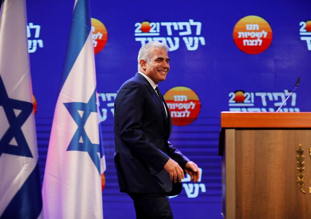 Yesh Atid party leader Yair Lapid walks towards the podium before delivering a speech following the announcement of exit polls in Israel's general election at his party headquarters in Tel Aviv, Israel March 24, 2021.