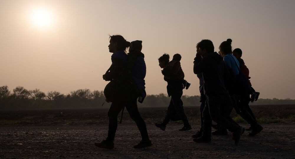 FILE PHOTO: Asylum-seeking mothers from Guatemala and Honduras carry their children after they crossed the Rio Grande river into the United States from Mexico on a raft, in Penitas, Texas, U.S., March 17, 2021.