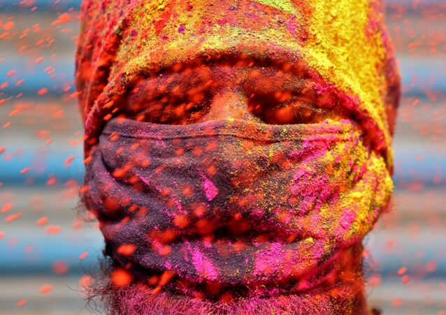 A man wearing a protective face mask reacts as colour powder is thrown towards him during Holi celebrations, amidst the spread of the coronavirus disease (COVID-19), in Chennai, India, March 29, 2021.