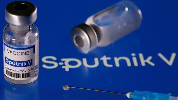 Vial labelled Sputnik V coronavirus disease (COVID-19) vaccine placed on displayed Sputnik V logo is seen in this illustration picture taken March 24, 2021. - Sputnik International