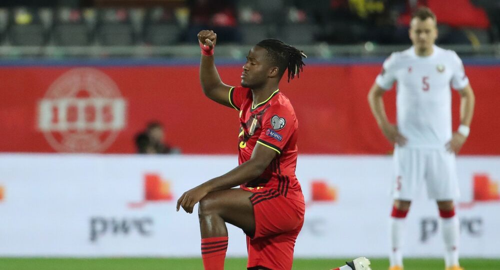Belgium's Michy Batshuayi kneels in support of the Black Lives Matter campaign before the match