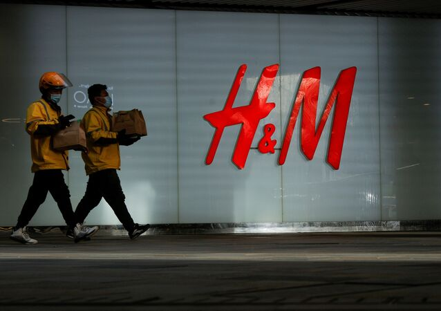 People walk past an H&M store in a shopping area in Beijing, China, March 28, 2021