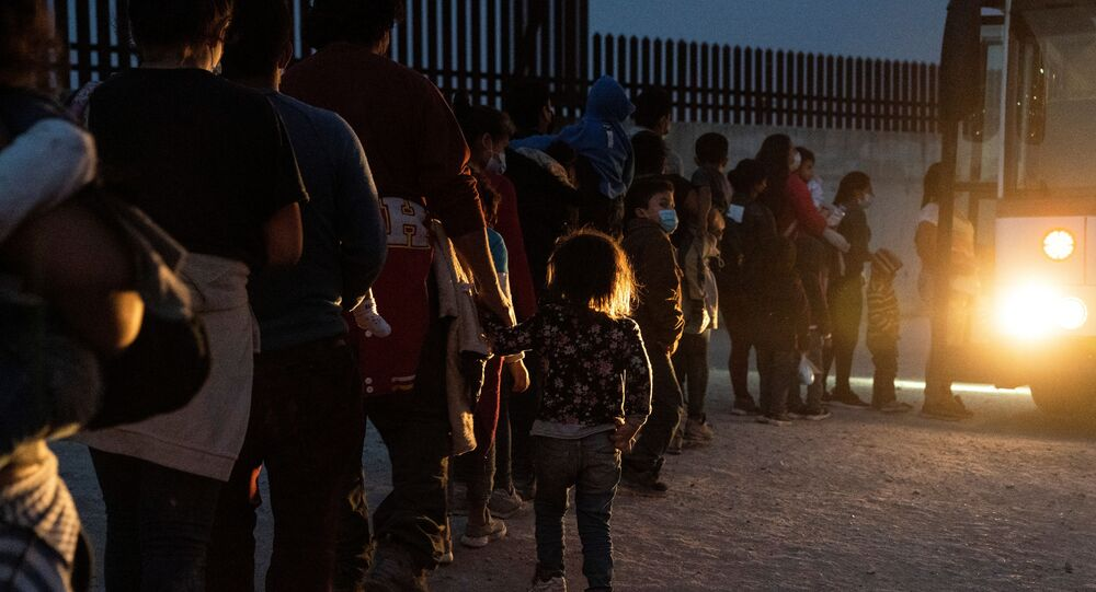 Asylum-seeking migrants' families make a line to board a bus as they wait to be transported by the U.S. Border Patrols after crossing the Rio Grande river into the United States from Mexico in Penitas, Texas, U.S., March 26, 2021