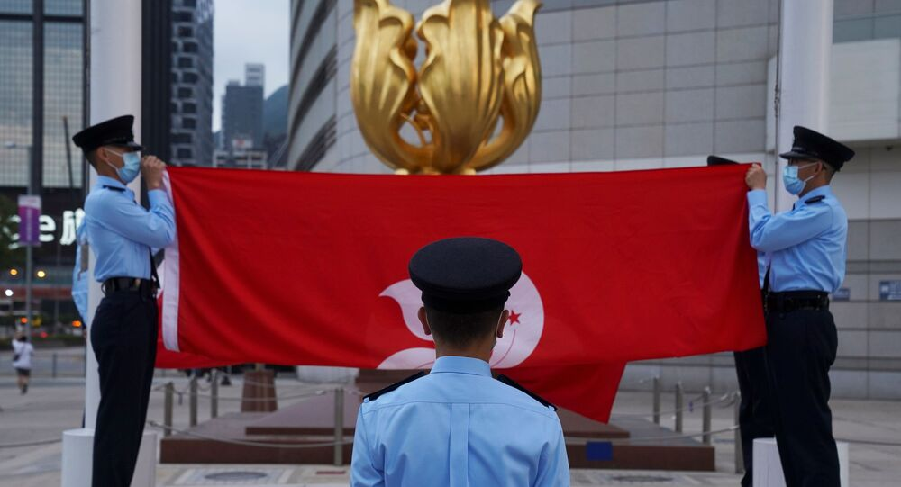 Police officers fold Chinese and Hong Kong flags at a flag-lowering ceremony in front of the Golden Bauhinia statue on the square, in Hong Kong, China March 30, 2021.