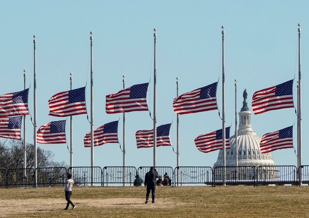 People walk past flags flying at half staff at the Washington Monument in memory of 500,000 deaths due to coronavirus disease (COVID-19) in Washington, U.S., February 24, 2021.