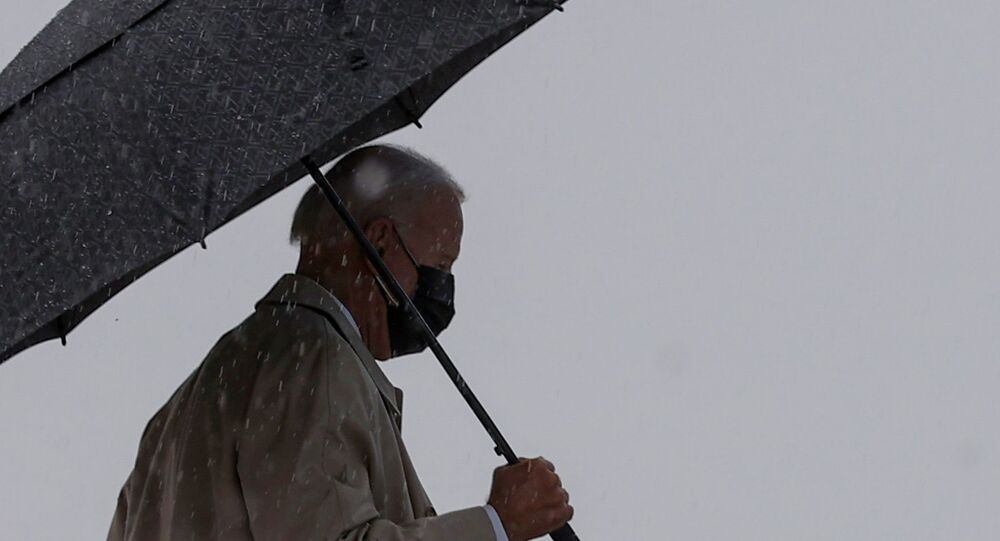 U.S. President Joe Biden walks in the rain prior to boarding Air Force One as he departs Washington for travel to Pittsburgh, Pennsylvania at Joint Base Andrews, Maryland, U.S., March 31, 2021.