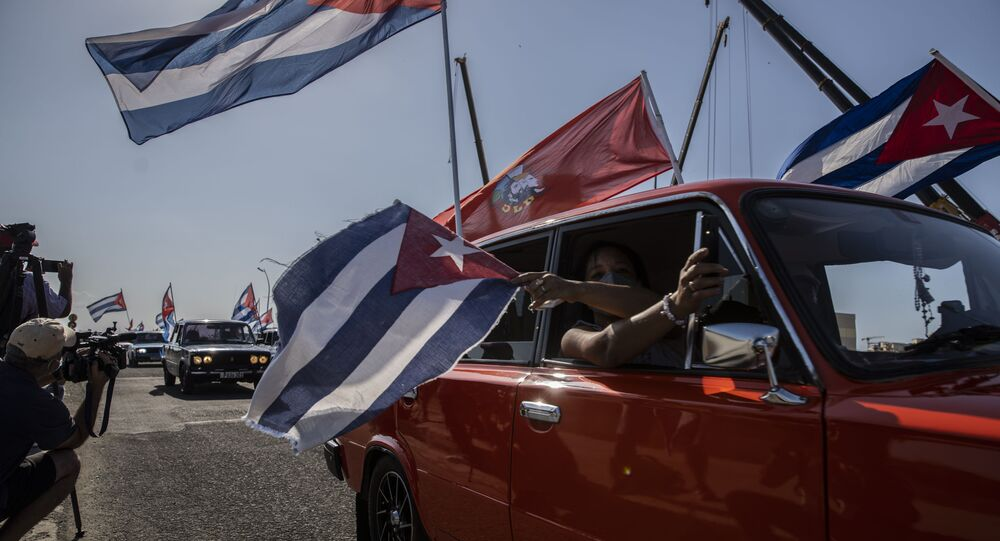 Soviet-era Lada cars flying Cuban flag drive past the American embassy during a rally calling for the end of the US blockade against the island nation in Havana, Cuba, Sunday, March 28, 2021