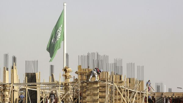 Egyptian workers assemble concrete forms at a building site as a giant Saudi flag hangs in the background at King Abdullah Square in Jiddah, Saudi Arabia, Sunday, March 14, 2021 - Sputnik International