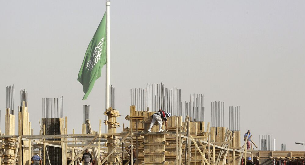 Egyptian workers assemble concrete forms at a building site as a giant Saudi flag hangs in the background at King Abdullah Square in Jiddah, Saudi Arabia, Sunday, March 14, 2021